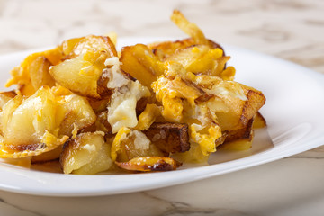 Fries with smashed eggs on white plate