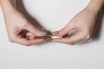 Hands of a woman rolling a cigarette with rolling tobacco on clear background.