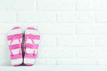 Pair of flip flops on the brick wall background