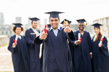 happy student with diploma pointing finger at you