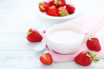 Strawberry yogurt in bowl on wooden table