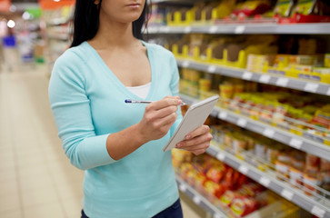 woman with notebook shopping at supermarket