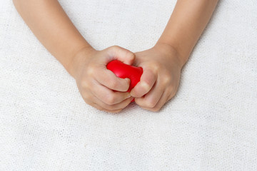 Red heart in baby palm hands