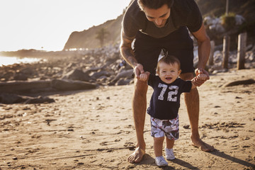 Father helping son (6-11 months) walk on beach