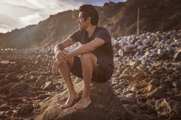 Man sitting on rock on pebbly beach
