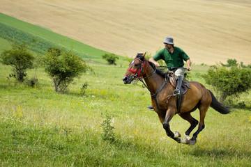 Man riding horse over green hills
