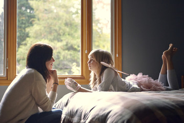 Mother and daughter (10-11) talking in bedroom
