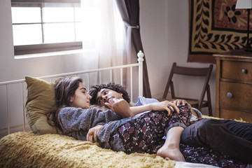 Couple lying in bed at home