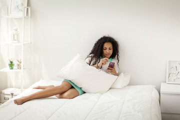 Young girl (12-13) using smart phone in bed