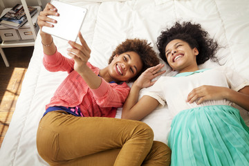 Young girls (12-13, 14-15) taking selfie with digital tablet
