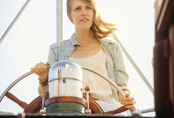 Young woman steering yacht