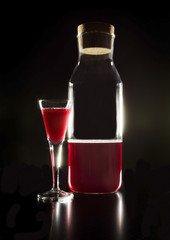 Glass and a bottle with red liquor