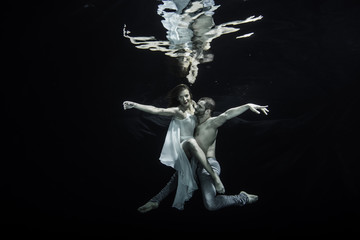 Young couple dancing underwater
