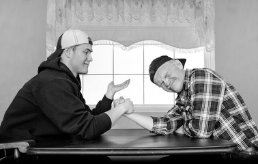 horizontal black and white image of a caucasian father and grown son having an arm wrestling challenge and being silly.
