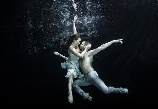 Young couple dancing underwater
