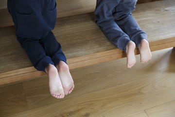 Two pairs of kids feet on a wooden bench, which stands on a wooden floor. The kids wear lounge gear and are bare feted.