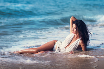 The beautiful model posing lying on the beach