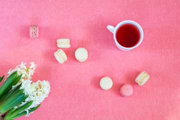 Beautiful spring holiday background. Cup of tea, fresh white hyacinth and sweet  berry and vanilla macaroons cookies on pink copy space groundwork.