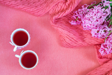 Beautiful spring holiday background. Two cups of tea, fresh white hyacinth and pink woven scarf on pink copy space groundwork.
