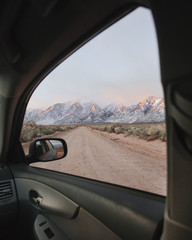 View through car window of snow capped mountains