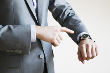 Close up of a businessman's hand pointing at clock on his wrist