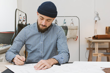 Male designer working in studio, sitting at table and drawing