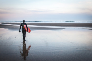 Surfer carrying red board towards sea
