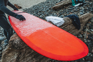 Surfer preparing red board with wax on pebbled beach
