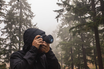 Man photographing with camera while standing against trees in forest