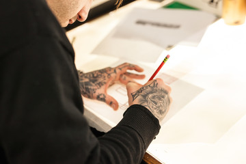 Man with tattooed hands drawing at light box
