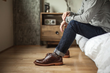 Man sitting on bed in jeans and shoes