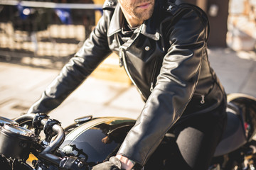 Man astride motorbike in black leather jacket and jeans