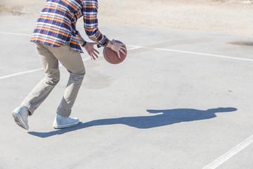 Man bouncing basketball on sunny day