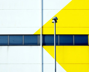 Yellow and white minimalist facade of a modern building with a street lamp