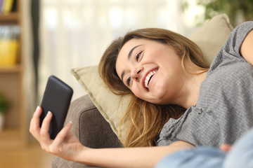 Teen watching videos in a smart phone at home