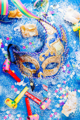 Carnivalesque composition. Top view of a carnival mask, whistles, corianders, and sfrappoles or chiacchere,italian fried carnival cookies with icing sugar on a bluish shabby chic board.