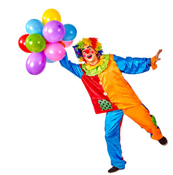 Birthday child clown with balloons bunch on isolated. Events organizer man is standing on one leg on white background.