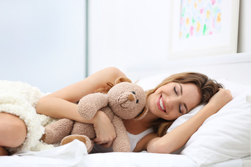 Young beautiful woman lying on bed with teddy bear