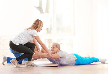 Physiotherapist working with elderly patients in clinic