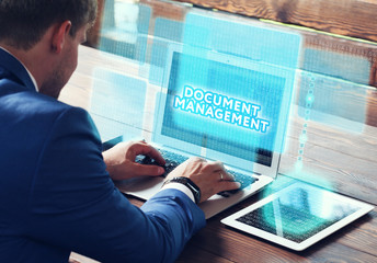Business, technology, internet and networking concept. Young businessman working on his laptop in the office, select the icon Document management on the virtual display.