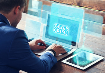 Business, technology, internet and networking concept. Young businessman working on his laptop in the office, select the icon Cyber crime on the virtual display.
