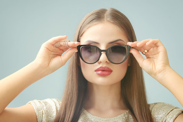 Portrait of beautiful young woman with sunglasses on colour background