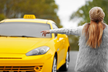 Woman catching yellow taxi cab on the street Fototapete