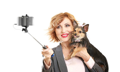 Beautiful middle aged woman with adorable little dog taking selfie on light background