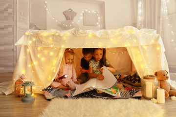 Cute little children reading book in hovel at home Wall mural