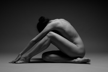 beautiful nude woman practicing yoga