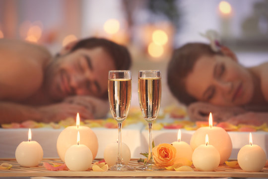 Beautiful spa composition with glasses and happy couple on background
