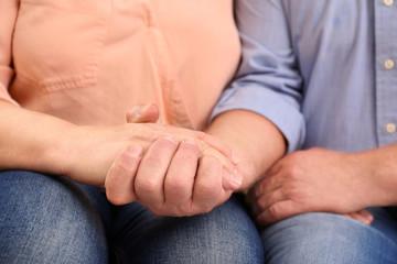 Closeup of husband holding wife's hand