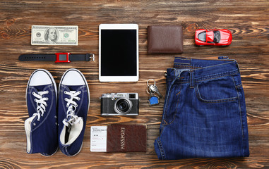 Flat lay of traveller's accessories on wooden background