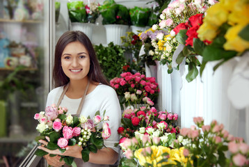 Pretty young florist with bouquet in flower shop